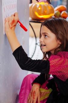 Datas no calendário. linda garota fofa com longos cabelos escuros usando um vestido de halloween cruzando as datas no calendário