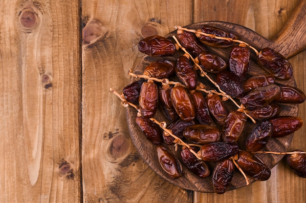 Datas orgânicas cruas de medjool prontas para comer. doces do leste em um fundo de madeira. copie o espaço.