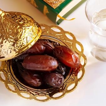 Datas orgânicas placa dourada árabe, copo de água potável pura e livro de alcorão.