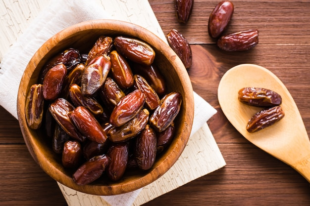 Datas secas doces frutas em uma tigela de madeira e na colher. vista do topo