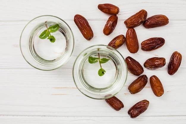 Datas secas frutas com água em taças