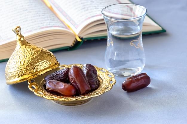 Datas secas orgânicas, copo de água potável pura e livro de alcorão