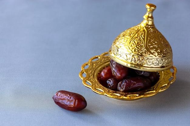 Datas secas orgânicas na placa dourada árabe tradicional.