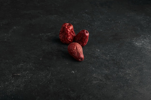 Datas secas vermelhas isoladas na superfície preta.
