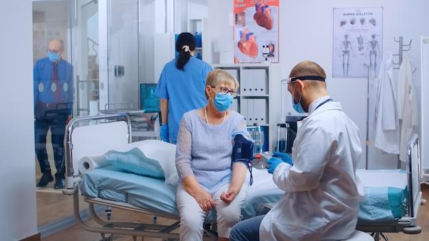 Dcotor, verificando problemas cardíacos de idosa aposentada durante a pandemia em uma clínica privada moderna ou hospital. paciente e material médico usando máscaras para proteção contra covid-19. saúde médica