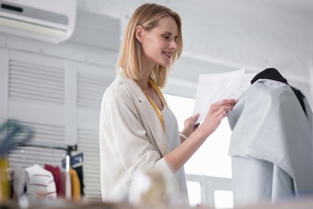 De acordo com esboços. costureira feminina positiva carregando esboços enquanto trabalha com o tecido