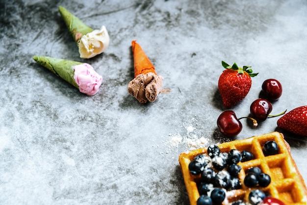 De alimentos refrescantes sorvetes em cones com frutas vermelhas e waffles, com espaço negativo para o verão.