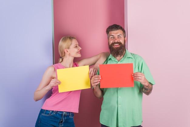 De anúncios. tabuleiro vazio. casal segura placas de publicidade. quadro de mensagens. anúncio. oferta. compras. copie o espaço para o texto. casal com tabuleiros vazios.