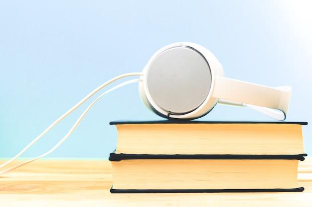 De audiobook. livros sobre a mesa com fones de ouvido