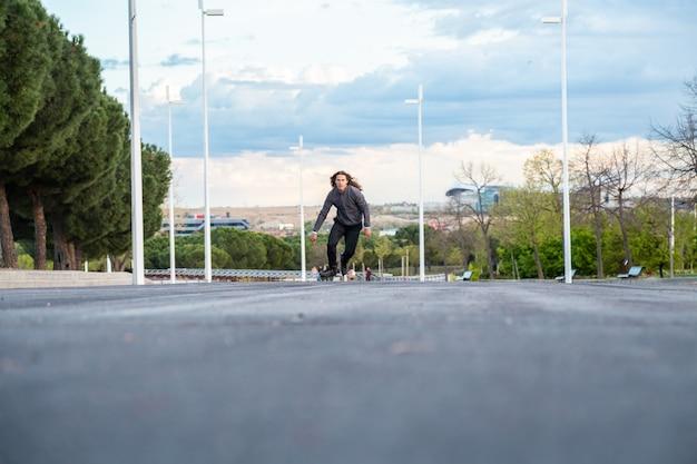 De baixo jovem homem legal no sportswear andando de patins muito rápido na estrada no parque