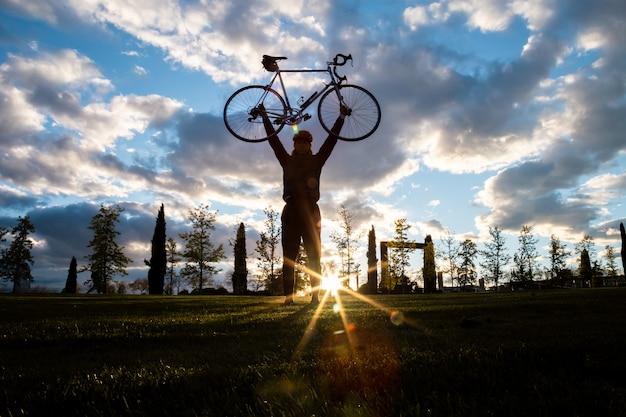 De baixo jovem macho bonito feliz, levantando as mãos com bicicleta no parque da cidade no pôr do sol em volta iluminado