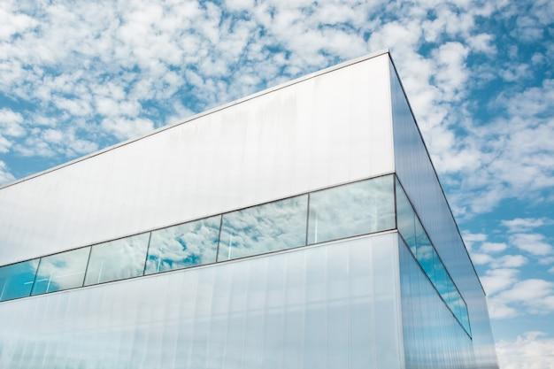 De baixo tiro de canto de vidro brilhante edifício empresarial moderno