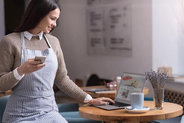 De bom humor. mulher bonita feliz usando laptop e sorrindo enquanto escreve uma massagem em seu celular.