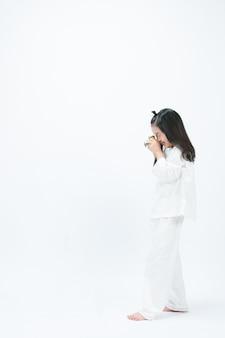 De branco, uma criança está filmando a frente com uma câmera.