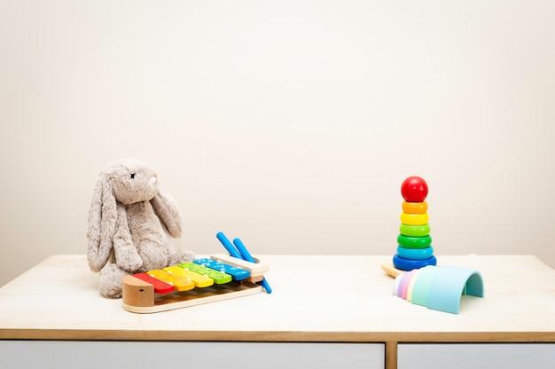 De brinquedos infantis coloridos contra a parede brinquedos na mesa de madeira com copyspace