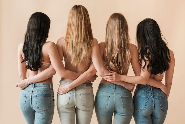 De cabelos compridos slim mulheres de pé juntos em linha