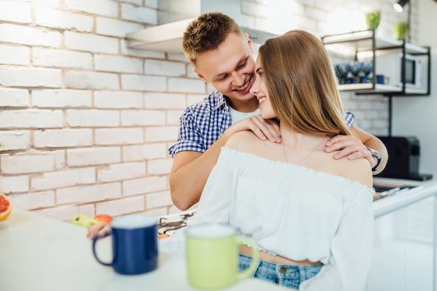 De casal na cozinha, homem fazendo massagem para sua mulher.