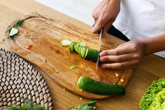 De cima, a mulher está cortando um pepino em uma mesa da cozinha