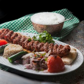 De cima adana kebab com arroz e legumes fritos e cebola picada e ayran
