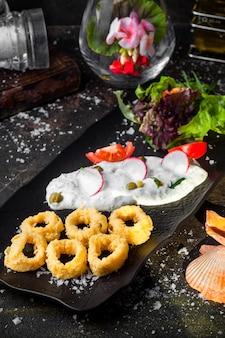 De cima, anéis de lula em massa com salada de legumes frescos e molho e flores na bandeja