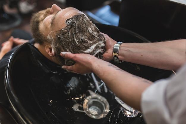 De cima barbeiro lavar o cabelo do cliente