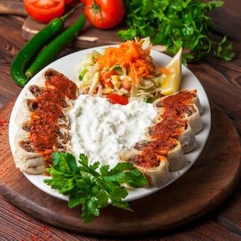 De cima beyti kebab com iogurte e limão e salada em chapa branca