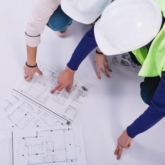 De cima construtores discutindo plantas