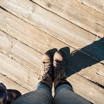 De cima de pernas no chão de madeira