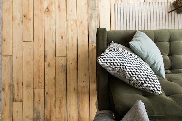 De cima de um tiro aconchegante sofá de cor verde escura com almofadas no interior