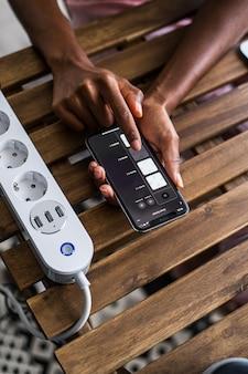 De cima de uma pessoa afro-americana anônima usando o aplicativo de casa inteligente no smartphone