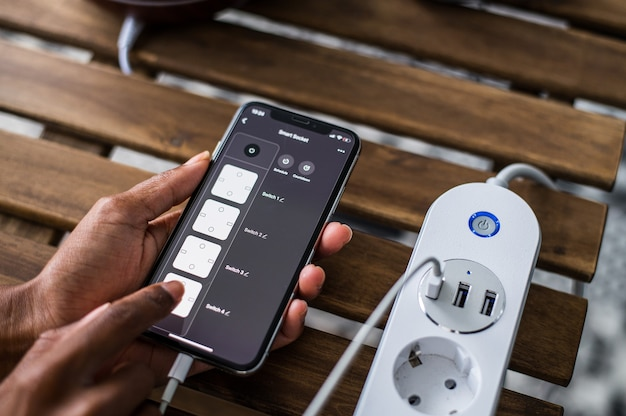 De cima de uma pessoa afro-americana anônima usando o aplicativo de casa inteligente