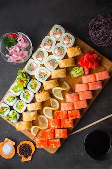 De cima do conjunto de sushi com molho de soja e os pauzinhos na tábua de madeira