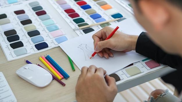 De cima do corte, alfaiate irreconhecível criando desenho de roupas em folha de papel