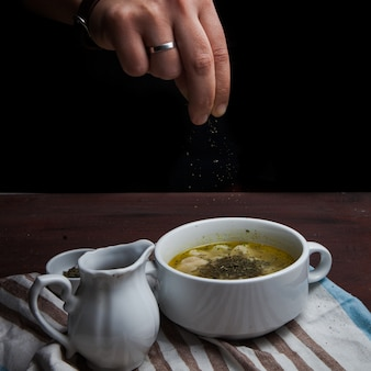 De cima dushpara com vinagre e hortelã seca e mão humana em prato fundo