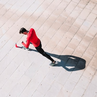 De cima, homem fazendo lança no pavimento