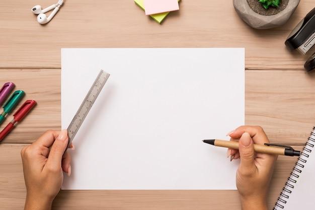 De cima mãos segurando régua e caneta sobre a folha de papel em branco