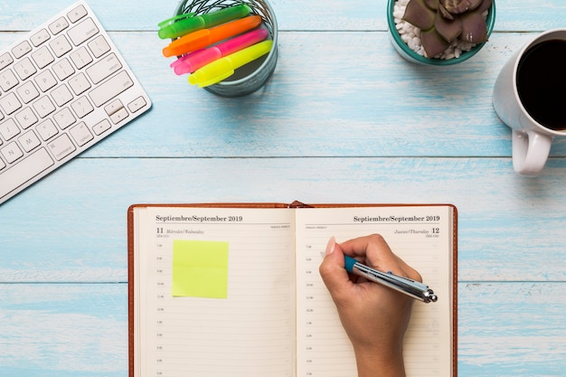 De cima mulher escrevendo no diário
