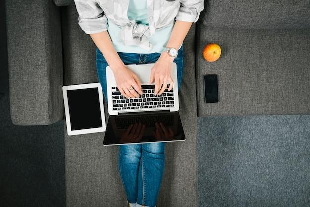 De cima mulher navegando laptop no sofá