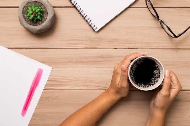 De cima mulher segurando café sobre o espaço de trabalho