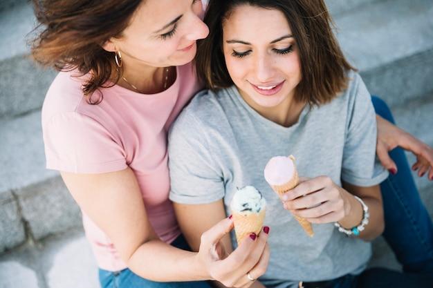 De cima mulheres comendo sorvete em etapas