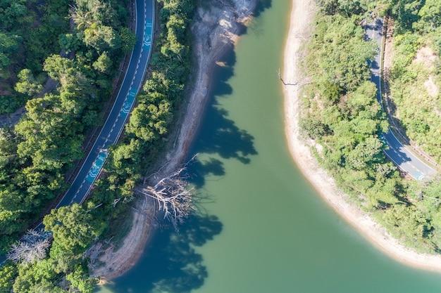 De cima para baixo da vista aérea do drone da floresta tropical com estrada de asfalto ao redor da barragem e terra compartilhada, cuidado com o sinal de bicicleta na estrada