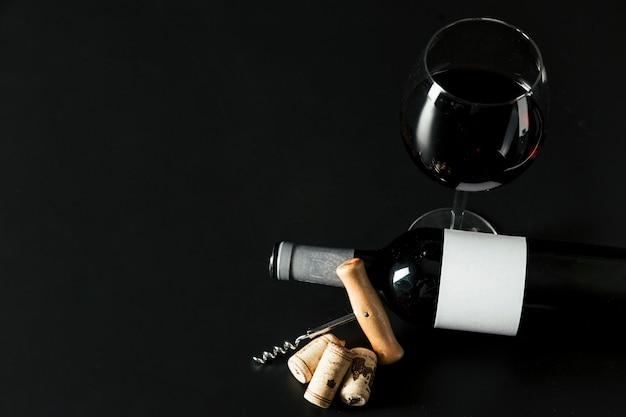 De cima saca-rolhas perto de garrafa e copo de vinho
