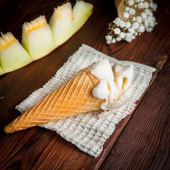 De cima sorvete em um cone de waffle com fatias de melão e gypsophila em guardanapos de pano
