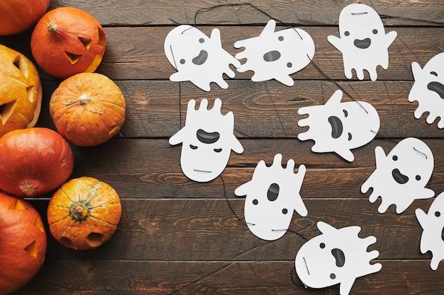 De cima, uma cena plana de abóboras esculpidas e fantasmas de papel fofos para o halloween, deitados na superfície da mesa de madeira marrom escura