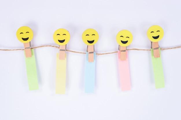De cinco carinhas alegres com reações diferentes penduradas em uma corda segurando adesivos de papel na parede branca