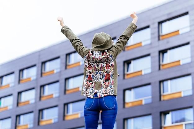De costas irreconhecíveis que virou jovem com os braços erguidos feliz na rua