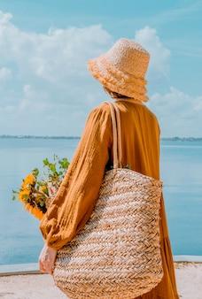 De costas, jovem descansando na praia menina com chapéu de palha apreciando a bela vista fotos de costas