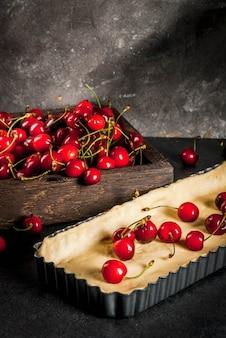 De fazer uma torta de cereja. cerejas frescas em uma bandeja de caixa de madeira rústica, um formulário para assar com uma massa. em uma mesa de cozinha preta copyspace