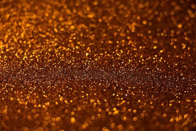 De foco, plano de fundo de luzes de glitter abstratas. azul, dourado e preto.