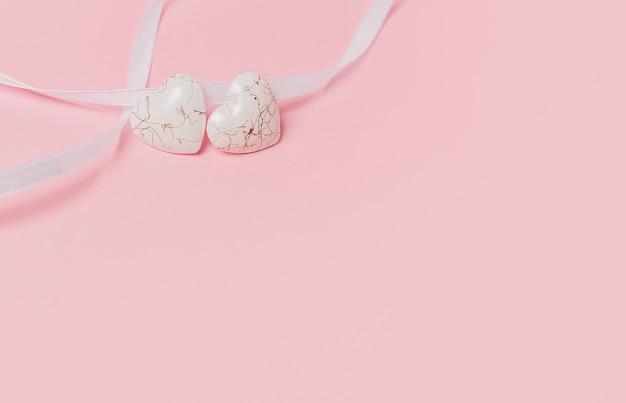 Dê forma a um coração com uma fita wihte em um fundo rosa isolado